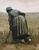 A woman facing away working with a spade