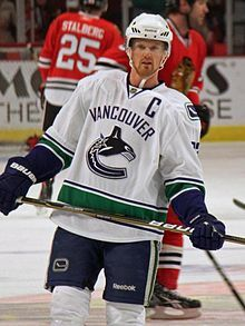 """An ice hockey player wearing a white and blue jersey with a logo of a stylized orca in the shape of a """"C"""". He stands relaxed on the ice looking forwards."""