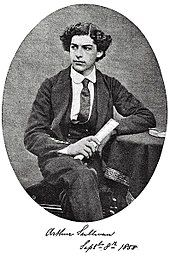 Sullivan seated with one leg crossed over another, age 16, in his Royal Academy of Music uniform, showing his thick, curly hair. Black and white.