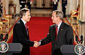 Tony Blair and George W. Bush shaking hands at a press conference.