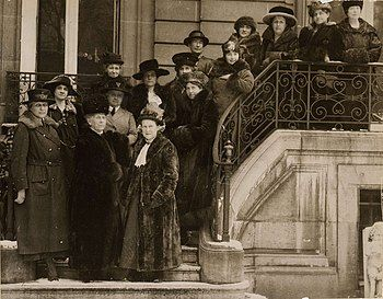 A black and white group photograph of 15 women in Edwardian dress posing on the outdoor entrance stairs
