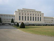 A drive leads past a manicured lawn to large white rectangular building with columns on it facade. Two wings of the building are set back from the middle section.