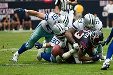 Photograph of defensive players tackling an offensive player who has just lost control of the football