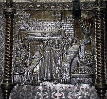 A bishop surrounded by people on their knees receive a bearded man wearing a crown in the port