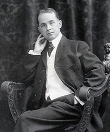 A black and white photograph of a middle-aged man in a suit posing reclined in a chair