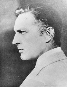 A cleanshaven Barrymore, seen from behind, over his left shoulder, glaring to his left