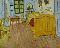 A small room with paintings on the wall, two chairs, a single bed and a table