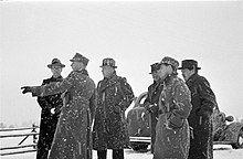 A group of foreign journalists observing something during snowfall in Mainila, where a border incident between Finland and the Soviet Union escalated into the Winter War.