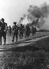 Several soldiers walking away from a burning house.