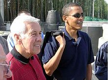 Gray-haired man and Obama stand, wearing casual polo shirts. Obama wears sunglasses and holds something slung over his right shoulder.