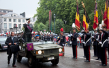 King Albert II in a vehicle saluting soldiers