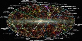 A map of the universe, with specks and strands of light of different colors.