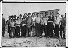 20–25 males facing camera in a row, mostly children. Ages vary. They are in work clothes. Some are dirty. Some wear caps. They stand on dirt with a wooden building behind them.