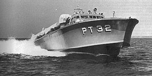 """a powerboat speeds across the water, riding high so the hull is exposed. """"PT 32"""" is painted on the hull in large white letters."""