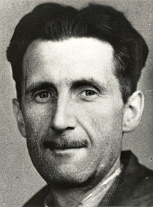 Photograph of the head and shoulders of a middle-aged man, with black hair and a slim mustache