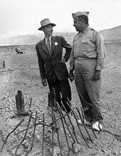 两名男性站在一堆变形的金属旁,一人身着西装,笑着望向另一穿着军装的男子。