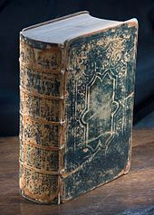 Studio photograph of a very old Bible standing vertically on a wooden surface with the spine turned three quarters of the way towards the viewer. The cover is black leather and is cracked and worn.