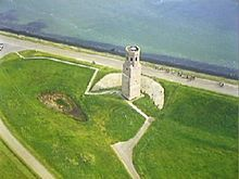 Aerial photograph of a white stone tower near the shore