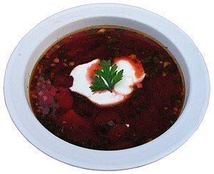 A bowl of dark-red borscht garnished with a dollop of sour cream and a parsley leaf