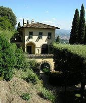 A yellow stucco building with a red clay roof and several arched doors and windows, surrounded by green shrubs.