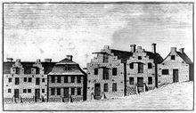 A black and white etching shows a number of houses along a street, many with stepped gables, which are classic Dutch architectural attributes.