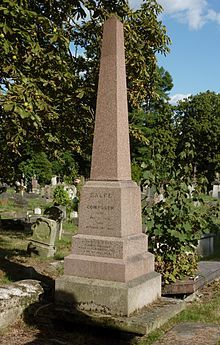 A red granite obelisk surrounded by other gravestones