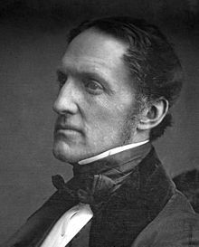 A black-and-white photograph of a middle-aged man wearing formal mid-19th century clothing facing left.