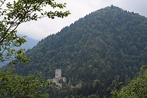 Photograph of stone fortress in wooded mountains.