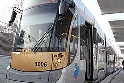 A grey tram with a logo on the side