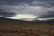 A landscape shot of a long, dry valley. The sky is partially clouded over but blue sky breaks through in patches. It is a showcase of Nevada's natural beauty.