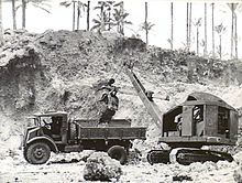 Black and white photo of a mechanical digger dropping soil into the tray of a truck