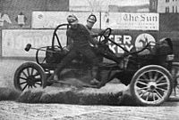 A malletman balances on the side of a moving auto polo car during a match in 1913.