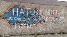 """White spray painted text on a tan wall that reads """"НАТО СЕ УБИЈЦИ ЈАС СУМ СПАС ЗА МАКЕДОНИЈА#БОЈКОТ"""" which translates to """"NATO are killers. I am for the salvation of Macedonia.#Boycott."""""""
