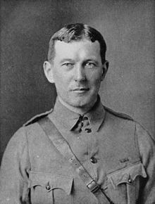 Upper body of a man in a soldier's uniform. He has short dark hair parted in the middle and maintains a neutral expression.