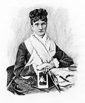 A middle-aged woman wearing her hair up on her head, wearing a dark dress with a large white collar