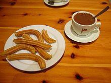 """画面右侧是一杯浓稠、微微冒泡的热巧克力,一个不锈钢勺子插入巧克力中,杯子放置在杯垫上,杯身写着""""ITAL CAFFÈ""""。左侧是一盘六根交叠、弯曲的西班牙油条,每根呈长条状,表面有顺着长边的凹槽。"""