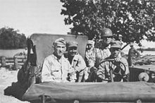 Four officers in a jeep, with a steel helmeted driver. The one on the left is wearing a garrison cap with three stars, the one in the center a cloth peaked cap with one star, while the one on the right had a steel helmet with two stars.