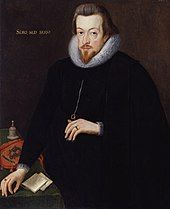 """A three-quarter portrait of a white man, dressed entirely in black with a white lace ruff. He has brown hair, a short beard, and a neutral expression. His left hand cradles a necklace he is wearing. His right hand rests on the corner of a desk, upon which are notes, a bell, and a cloth carrying a crest. Latin text on the painting reads """"Sero, Sed, Serio""""."""