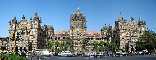 A brown building with clock towers, domes and pyramidal tops. Also a busiest railway station in India.[312] A wide street in front of it