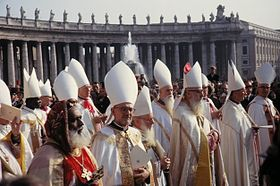 Many bishops robed in while stand in the sunshine in St Peter's Square. Most wear white mitres on their heads, except a black bishop in the foreground who wears a distinctive, embroidered velvet hat.