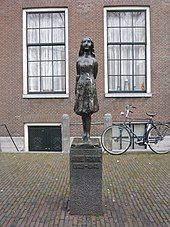 """A bronze statue of a smiling Anne Frank, wearing a short dress and standing with her arms behind her back, sits upon a stone plinth with a plaque reading """"Anne Frank 1929–1945"""". The statue is in a small square, and behind it is a brick building with two large windows, and a bicycle. The statue stands between the two windows."""
