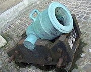 Photo of a short mortar with a wide bore. The pale green mortar rests on what looks like a rusted iron carriage.