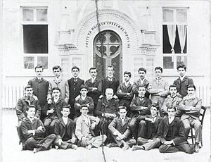Three rows of Pontic Greek men and boys in front of a school. They wear western suits.
