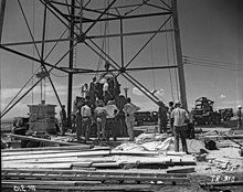 一群人站在像石油平台一样的结构附近,他们中间有一个巨大的球体正被吊起。