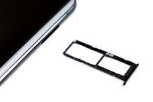 The sim tray of a ZenFone 6 adjacent to the sim tray receptacle of the phone