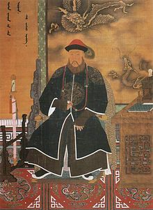 Three-quarter painted portrait of a thickly bearded man wearing a red hat adorned with a peacock feather and dressed with a dark long robe with dragon patterns. Clockwise from bottom left to bottom right, he is surrounded by a sheathed sword mounted on a wooden display, Manchu writing on the wall, a three-clawed dragon and a five-clawed dragon (also printed on the wall), and a wooden desk with an incense burner and a book on it.