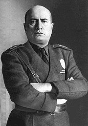 official portrait of Mussolini in uniform with crossed arms