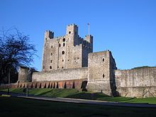 A photograph of a tall stone castle keep; most of the towers are square, but one is circular.