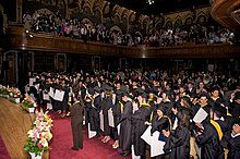 Young adults wearing ceremonial black robes and graduation caps stand at their seats in an ornate hall while onlookers in a three sided balcony applaud above them.