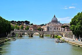 A view of Rome on a sunny afternoon looking along the river. A bridge crosses the river and beyond it is a hill on which the grey dome of St. Peter's rises above ancient buildings and dark pine trees.